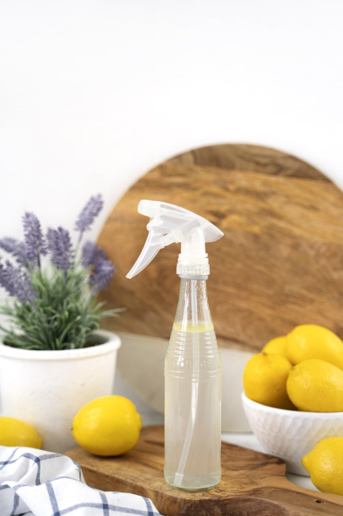 Bottle of DIY glass cleaner with bowl of lemons