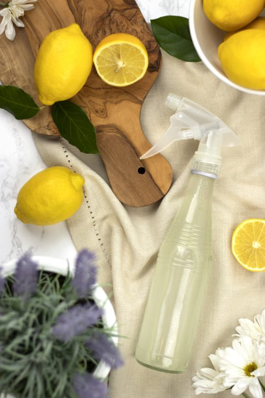 Bottle of homemade glass cleaner with lemons and cutting board