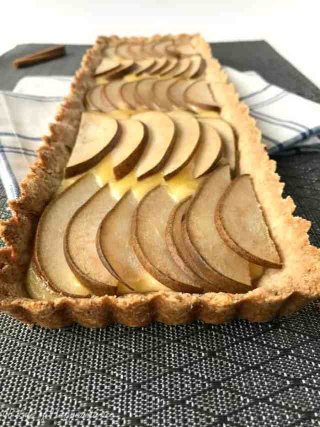 Pear and Havarti tart on a grey placemat.