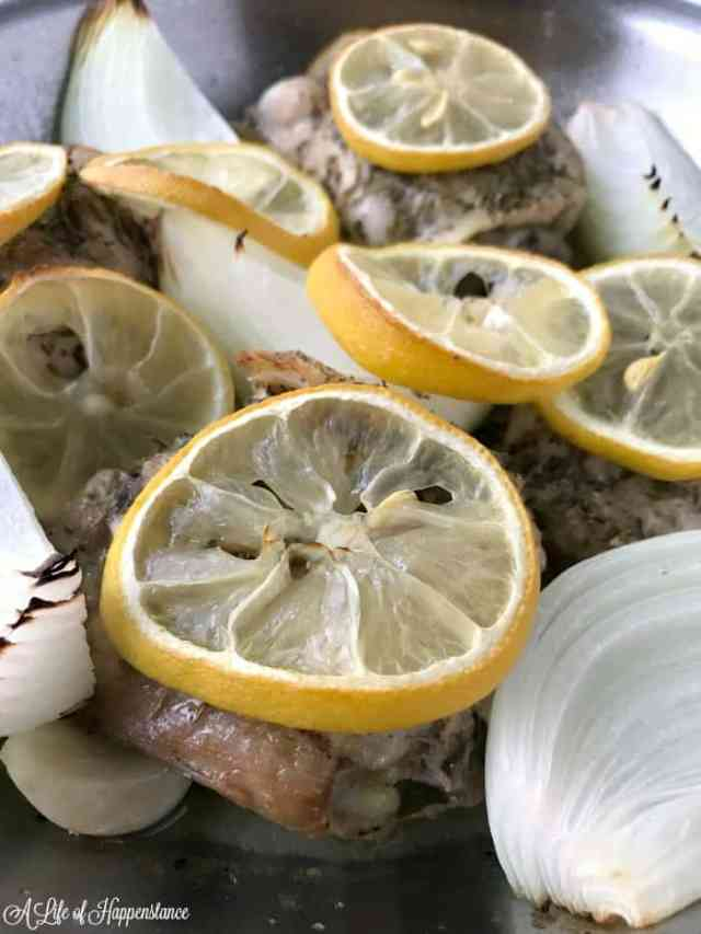 Close up shot of baked chicken thighs with onion wedges and sliced lemons.