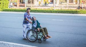 elderly woman sitting in on a wheelchair and being pushed by a gentle person along the road