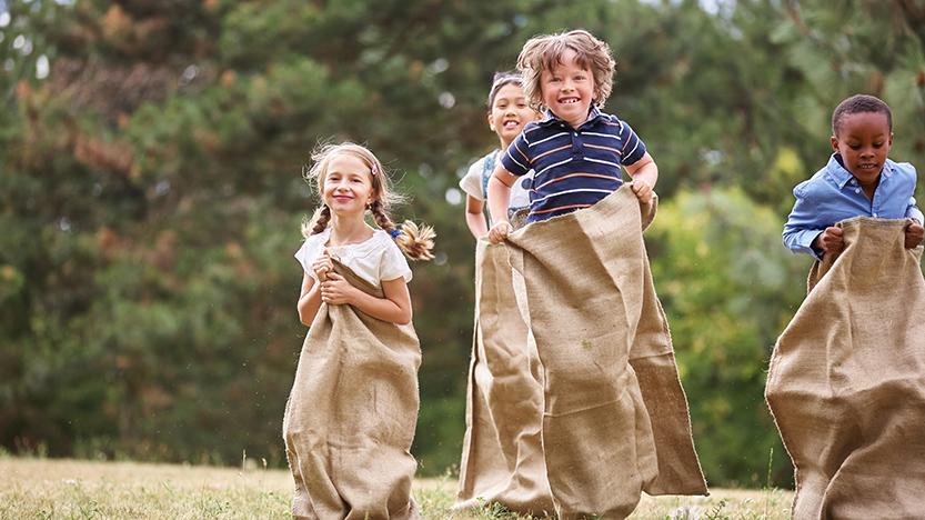 Crianças divertem-se a fazer uma gincana - corrida de sacos
