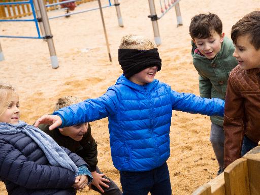 Criança vendada a brincar com outras crianças
