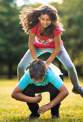 Várias crianças dobradas sobre si próprias, com outra a saltar por cima delas