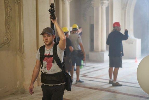 """Roman, carrying the """"crane"""" arm of the steady cam system"""