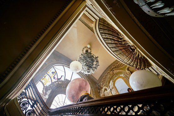 The location of the balloons under the stairs chandelier, and how the camera will see this action