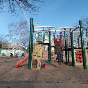 Woman hanging from monkey bars