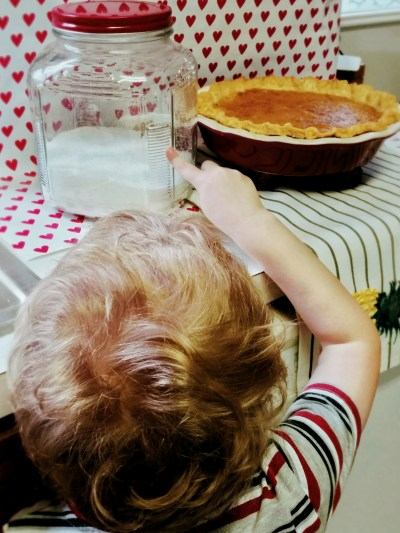 child helping make a salted caramel custard pie