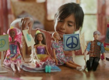 child playing with inclusive barbie dolls