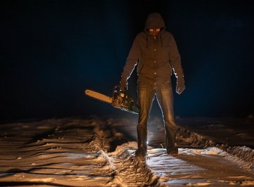 man in shadows, holding chainsaw