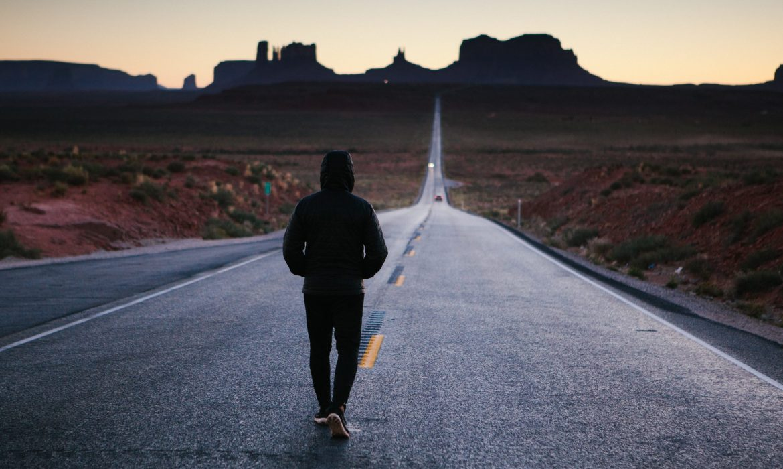 person walking down long road