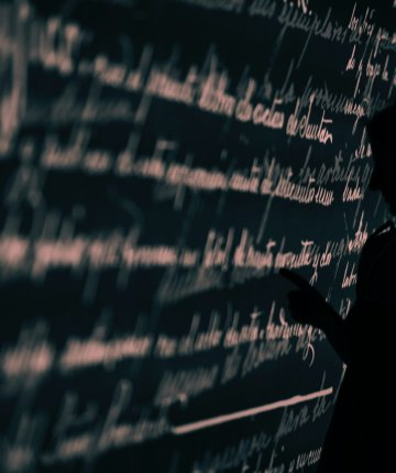 silhouette person writing on chalkboard