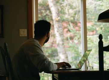 man at desk looking out window
