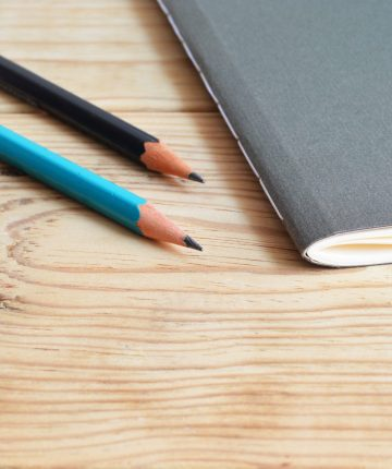 two pencils beside notebook
