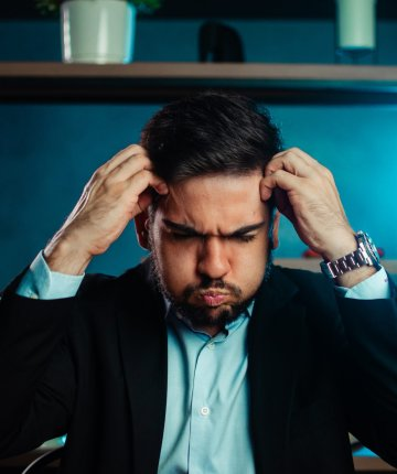 overwhelmed man holding head