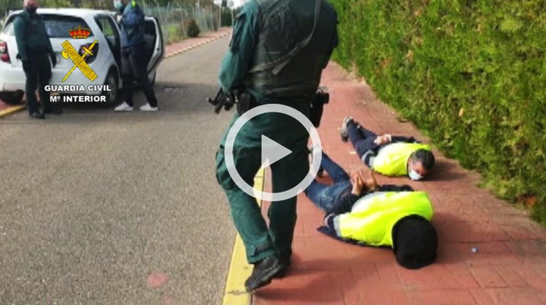Dos de los detenidos, esposados en el suelo frente a la casa de Palomares.