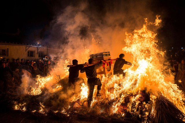 Men carrying a shrine jump over a bonfire for good luck at a traditional Chinese lunar new year celebration in Jieyang, Guangdong province. [China Daily/Reuters]