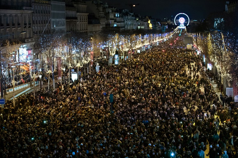 Revelers take part in New Year's Eve celebrations along Champs Elysees Avenue in Paris. [Philippe Wojazer/Reuters]