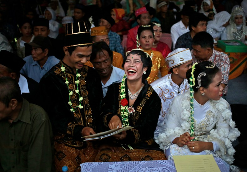 A bride and groom react to their marriage documents during a mass wedding held in celebration of the new year in Jakarta, Indonesia. Hundreds of couples took part in the mass marriage, held by the city government to help those unable to afford an individual wedding. [Dita Alangkara/AP Photo]