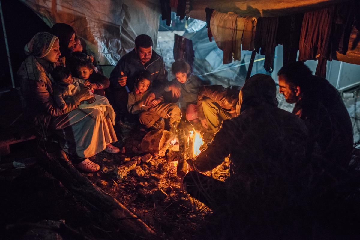Οι συριακοί και ιρακινοί αιτούντες άσυλο μοιράζονται ένα τζάκι ανάμεσα στις σκηνές τους.  Για πολλούς κατοίκους της κατασκήνωσης Moria, αυτός είναι ο μόνος τρόπος για να προστατευθούν από τις χειμερινές θερμοκρασίες.  [Kevin McElvaney / Al Jazeera]