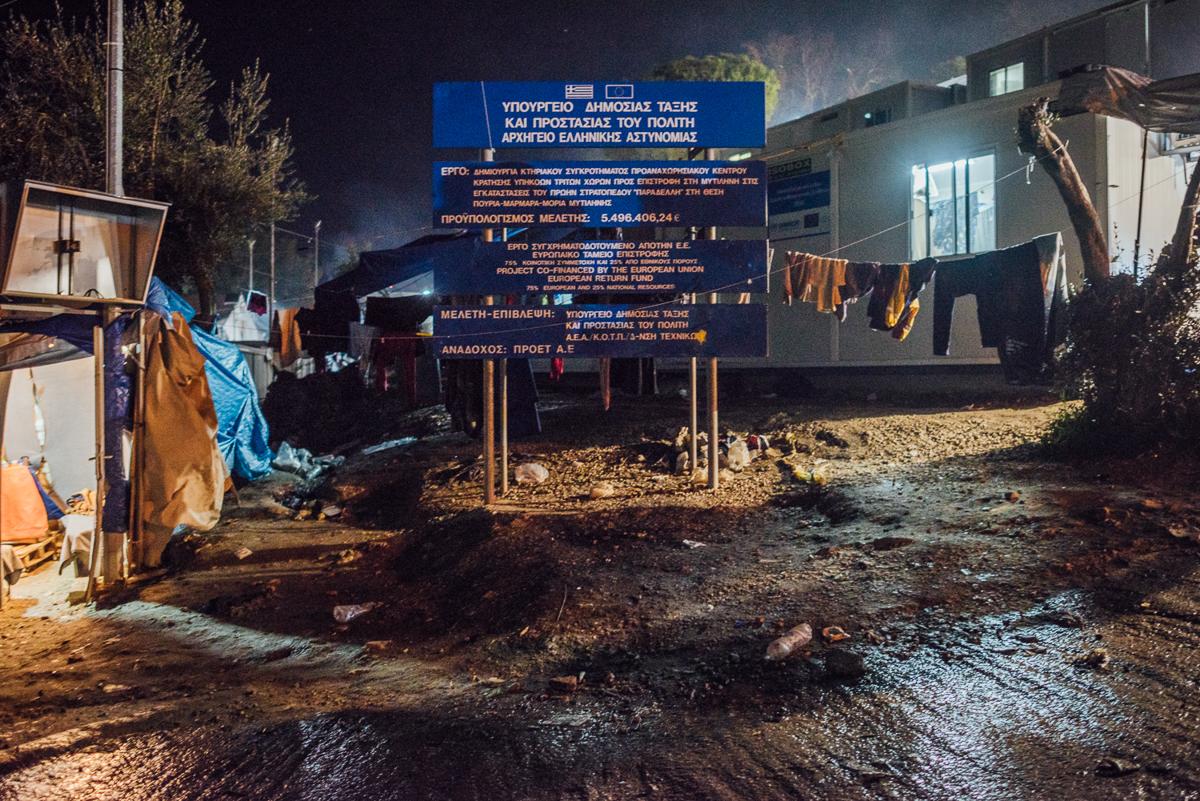 Ένα σημάδι αναφέρει ότι η ΕΕ και η ελληνική κυβέρνηση δαπάνησαν πάνω από 5,4 εκατομμύρια ευρώ (6,6 εκατομμύρια δολάρια) στον στρατόπεδο Moria.  [Kevin McElvaney / Al Jazeera]