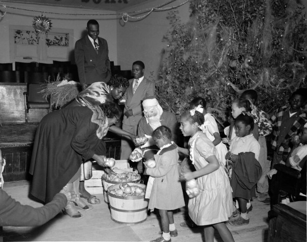 A man dressed as Santa Claus handing out Christmas gifts to children at a Fort Worth church in 1952. Unlike many segregated cities, where blacks lived only in one section, blacks in Fort Worth lived in every quadrant of the city. There was a thriving black downtown business district, with hotels, restaurants, a movie theatre, a bank, and a major hospital, pharmacy and nursing school, in addition to schools and churches - all eventually seen through Littlejohn's lens. [Calvin Littlejohn; Calvin Littlejohn Photographic Archive, Briscoe Center for American History]