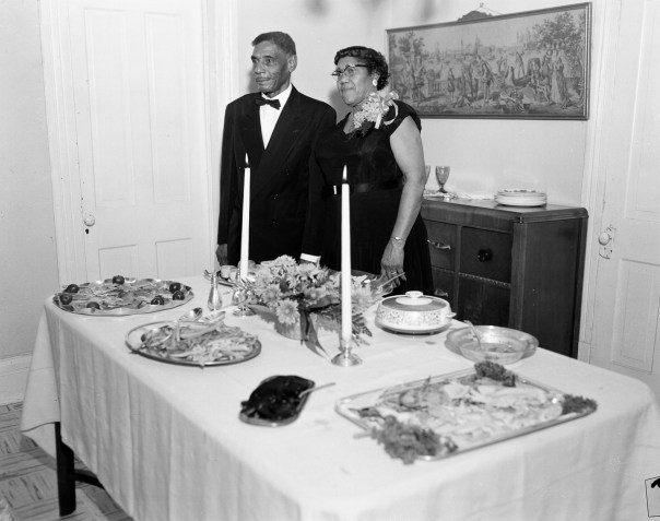 A couple posing behind the refreshment table at the celebration of their 50th wedding anniversary. Littlejohn's work provides a comprehensive portrait of the African-American experience in Fort Worth and the surrounding Tarrant County during segregation and beyond, offering a stark alternative to images of civil rights protests and marches that dominated media at the time and came to represent the African-American experience. [Calvin Littlejohn; Calvin Littlejohn Photographic Archive, Briscoe Center for American History]