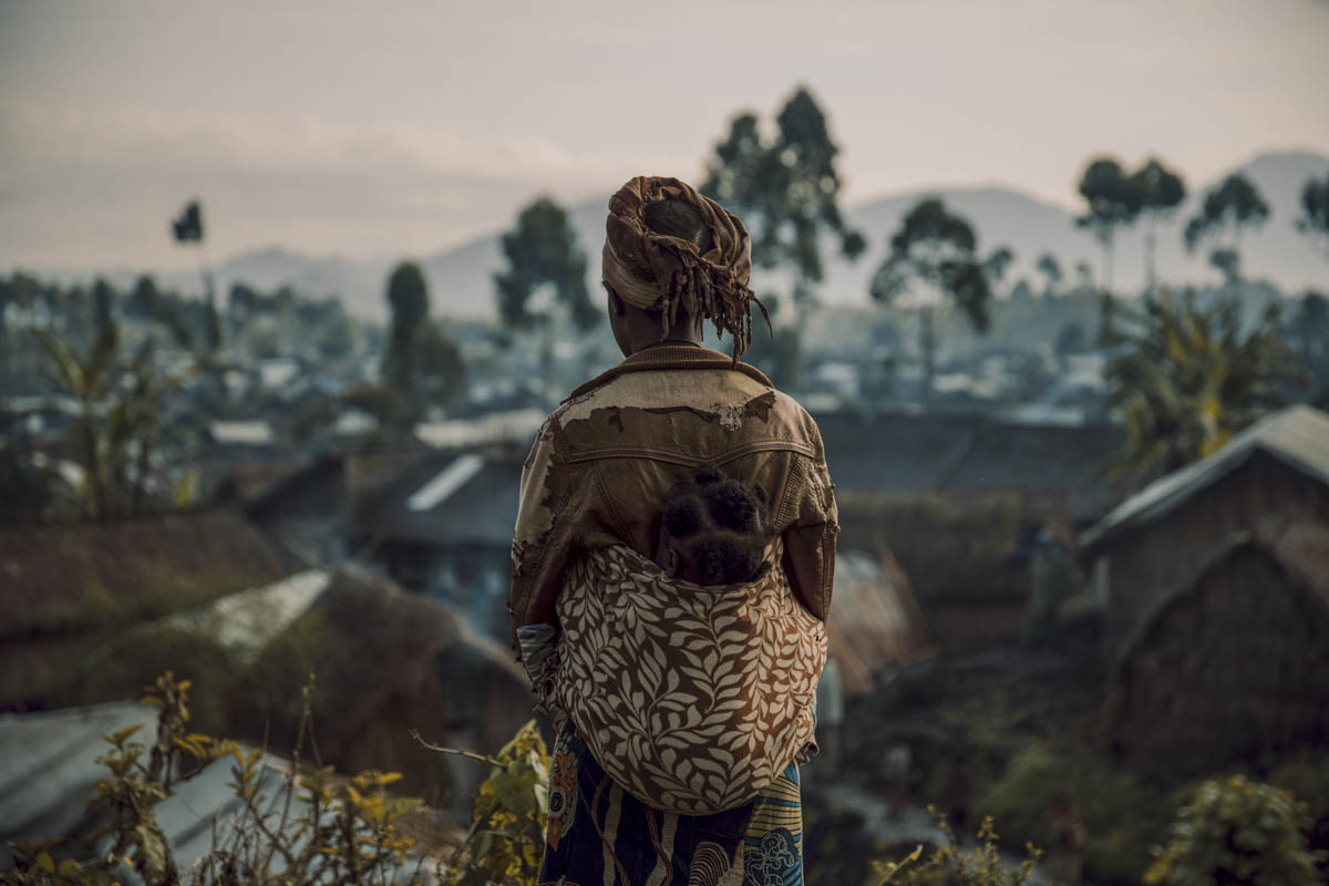 Sarah, 16, overlooks a camp for communities displaced by conflict in North Kivu, DRC. Sarah fell pregnant following a rape and now struggles to provide for her baby.Sarah was 15 when she was raped on her way back home from a visit to the hospital, in a vicious attack that left her pregnant. Her assailant, who then abandoned her, is now in jail. But for Sarah, his imprisonment gives little closure. She considers her life as destroyed. She wants to go back to school but currently struggles to afford food or provide for her baby's basic needs. [Hugh Kinsella Cunningham/Save the Children]