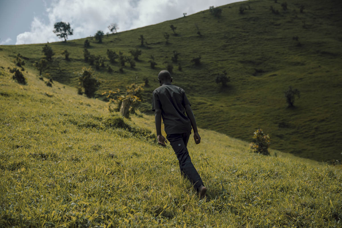 Former child soldier Nsii walks in the hills of North Kivu, DRC, after fleeing an armed group. When conflict broke out, Nsii was recruited by friends to join the local armed group, lured by the promise of a good salary and rewards. During an initiation ceremony, the group's commander cut Nsii's skin and smeared a 'juju' potion on his body. This, he was told, would make him invincible during the fighting. Nsii is currently being rehabilitated back into the community with the help of local NGO CAJED. [Hugh Kinsella Cunningham/Save the Children]