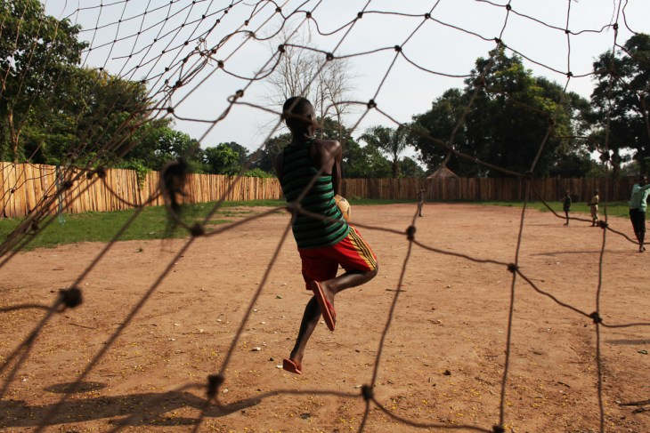 A 16-year-old boy who was a bodyguard in the opposition group South Sudan National Liberation Movement (SSNLM) plays football outside the transit centre ran by World Vision and UNI. [Andreea Campeanu/Al Jazeera]
