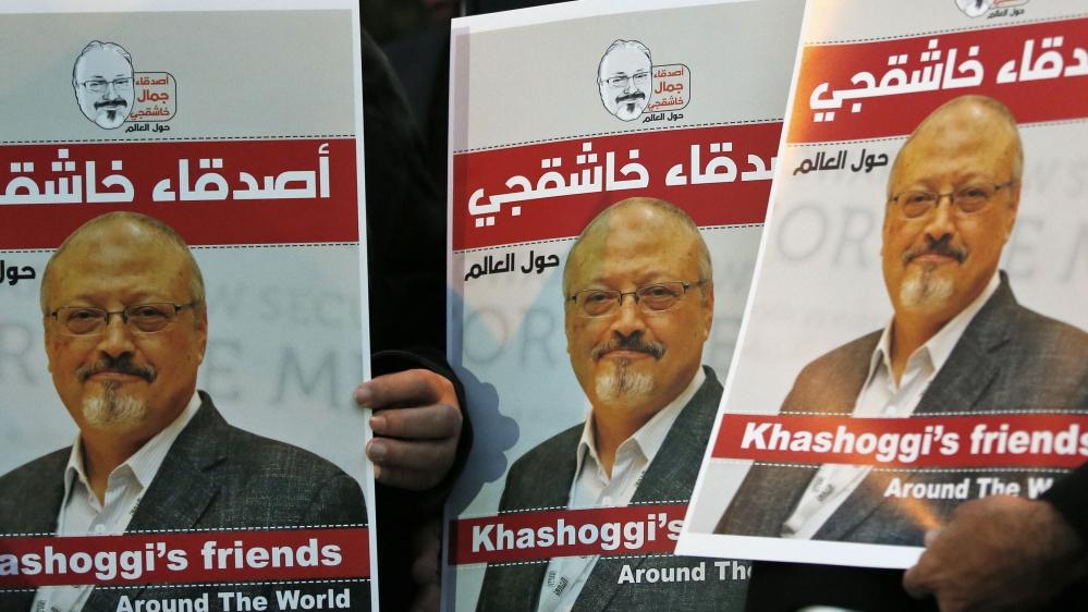 Activists protesting the killing of Saudi journalist Jamal Khashoggi hold a candlelight vigil outside Saudi Arabia's consulate in Istanbul, Thursday, Oct. 25, 2018. The posters read in Arabic:' Khas