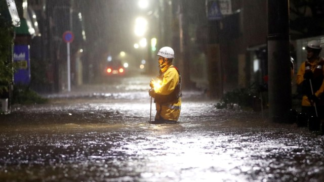 Firefighters patrol on a flooded road due to heavy rains caused by Typhoon Hagibis at Ota ward in Tokyo, Japan