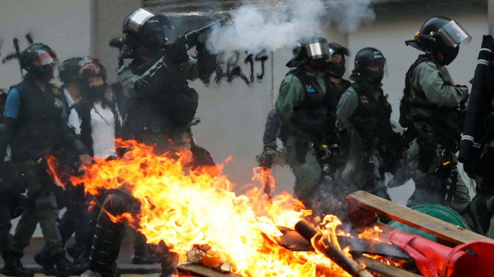 A police officer fires tear gas near a burning barricade during an anti-government protest in Hong Kong, China, October 20, 2019