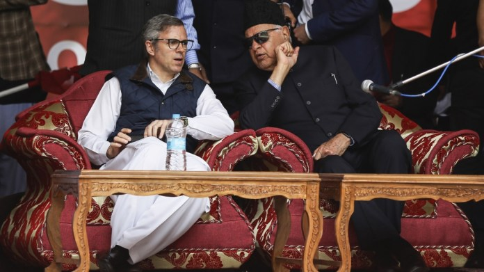 National Conference party president Farooq Abdullah, right and his son and former chief minister of Jammu and Kashmir Omar Abdullah, talk during an election rally in Srinagar, Indian controlled Kashmi