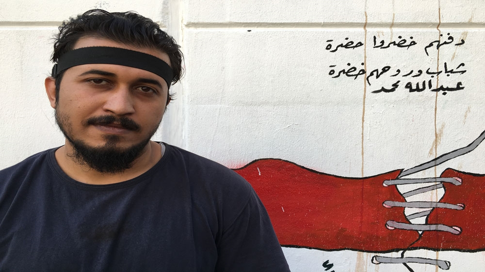 A protester stands in front of a mural in Baghdad