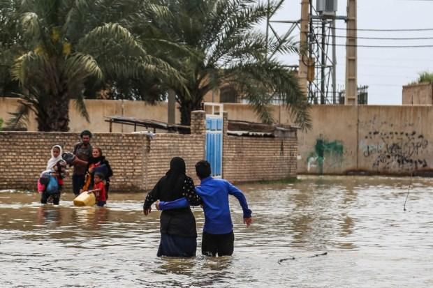 An Iranian family walks through a flooded street in a village around the city of Ahvaz, in Iran's Khuzestan province. [Mehdi Pedramkhoo /Tasnim News/AFP]