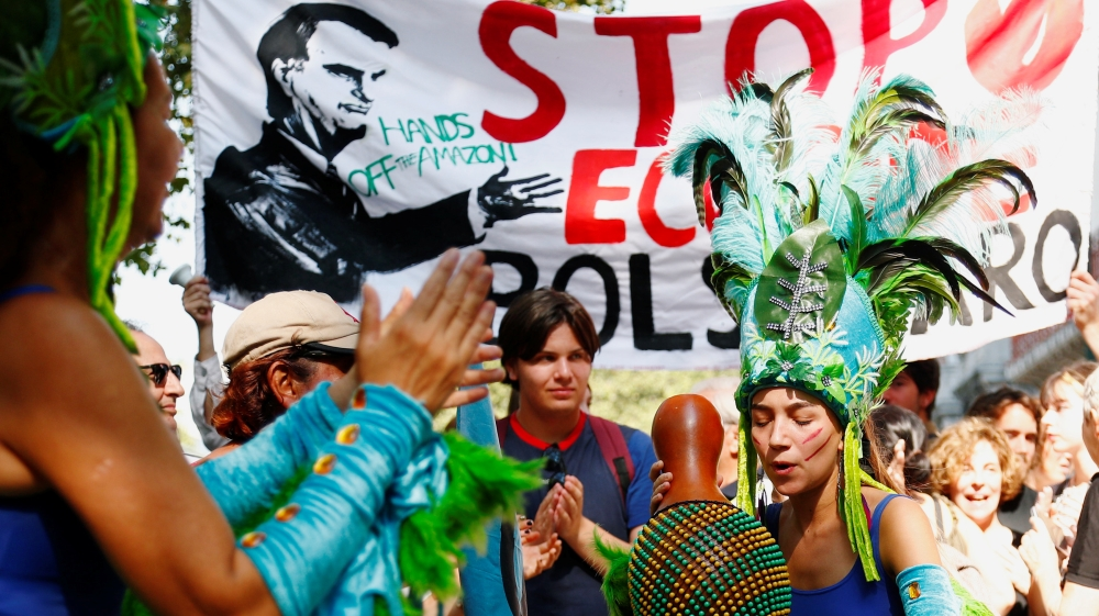Protesters dance during a demonstration to demand protection for the Amazon rainforest outside the embassy of Brazil in Brussels