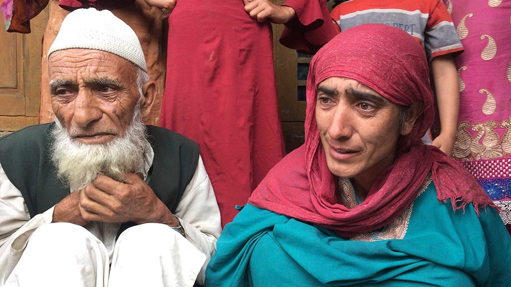 In this Monday, Aug. 26, photo, A Kashmiri man Mohammed Abdullah sits with his daughter at their home and talks to reporters about his grandson who was picked up in a nocturnal raid recently and shift