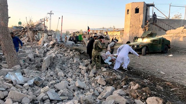 Afghan security members and people work at the site of a suicide attack in Zabul, Afghanistan, Thursday, Sept. 19, 2019. A powerful early morning suicide truck bomb devastated a hospital in southern A
