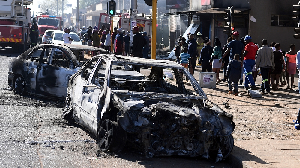 Pedestrians pass burnt out cars on the side of a street on the outskirts of Johannesburg, Monday Sept. 2, 2019. Police had earlier fired rubber bullets as they struggled to stop looters who targeted b
