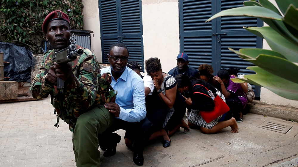 People are evacuated by a member of security forces at the scene where explosions and gunshots were heard at the Dusit hotel compound, in Nairobi, Kenya January 15, 2019. REUTERS/Baz Ratner