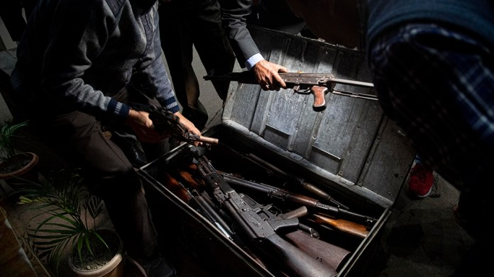 Assam police personnel pack up arms and ammunition handed over by cadres of different rebel groups after a surrender ceremony in Gauhati, India, Thursday, Jan. 23, 2020. More than 600 insurgents belon