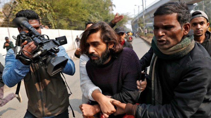 Wounded man is helped after an unidentified man opened fire during a protest against a new citizenship law outside the Jamia Millia Islamia university in New Delhi