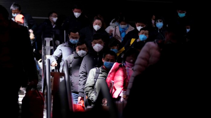 Passengers wearing masks are seen arrival at the Shanghai railway station in Shanghai