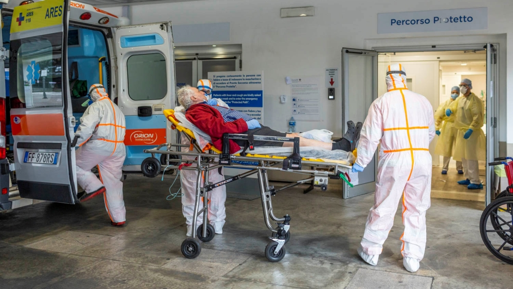 Medical workers in protective suits take an elderly coronavirus patient on a stretcher into an ambulance in the emergency room of the Gemelli Hospital, in Rome
