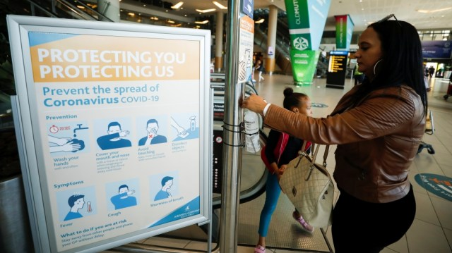 A traveller washes her hands at a sanitizer distribution point intended to slow the spread of the coronavirus disease (COVID-19), at Cape Town International Airport, in Cape Town
