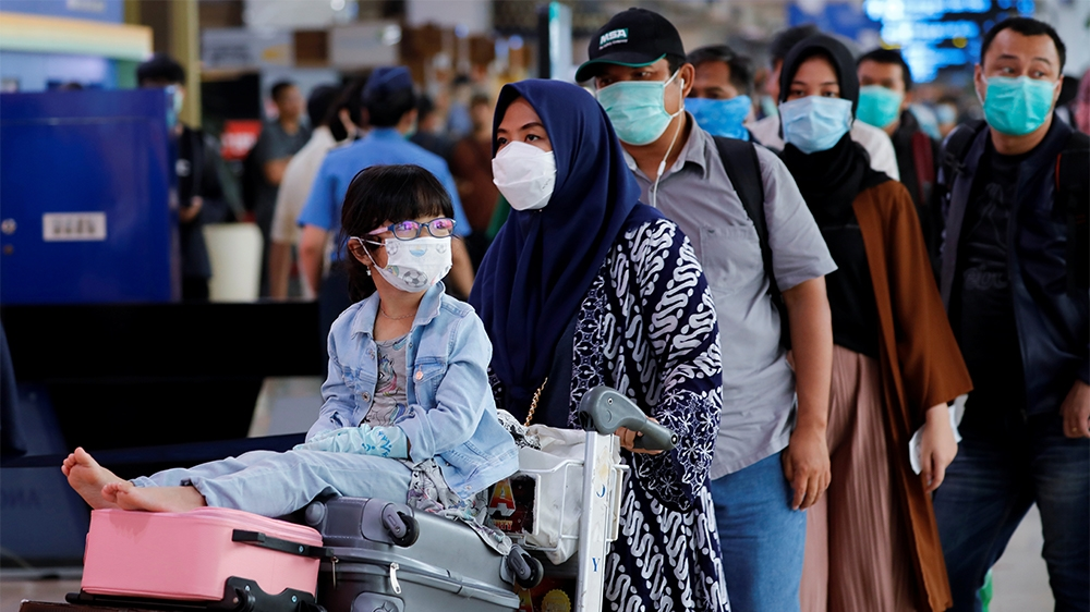 A girl wearing a protective face mask and synthetic gloves sits on luggages as she queues for temperature checking amid the spread of coronavirus disease (COVID-19) at Halim Perdanakusuma airport in J