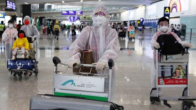 Passengers wear protective suits, amid the outbreak of coronavirus, at Hong Kong International Airport, Hong Kong, China March 17, 2020. REUTERS/Tyrone Siu