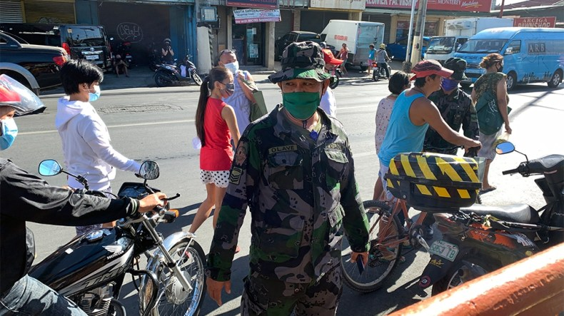 epa08317098 A soldier wearing a facemask stands guard in the street amid the ongoing coronavirus pandemic crisis, in Las Pinas, south of Manila, Philippines, 24 March 2020. According to the Department