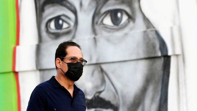 FILE PHOTO: A Saudi man walks past a poster depicting Saudi King Salman bin Abdulaziz, after a curfew was imposed to prevent the spread of the coronavirus disease (COVID-19), in Riyadh, Saudi Arabia M